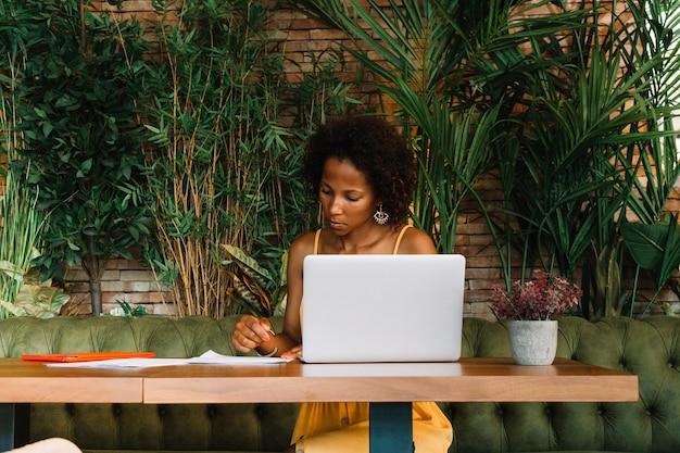 Documentos de la lectura de la mujer joven con el ordenador portátil en la tabla en el restaurante