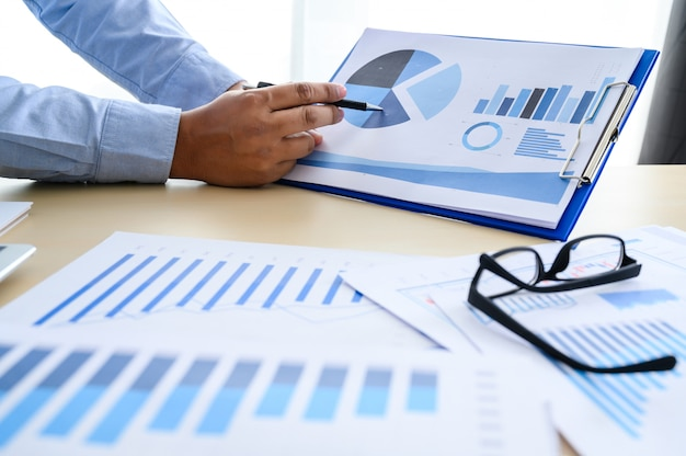 Documentos de negocios en el gráfico de la oficina financiera con un diagrama de red social que discute datos de análisis de datos los cuadros y gráficos