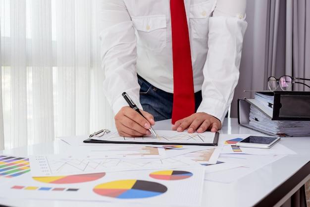 Documentos de negocios en la mesa de la oficina con teléfono inteligente y tableta digital y funcionamiento del hombre