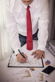 Documentos de negocios en mesa de oficina con teléfono inteligente y tableta digital y hombre trabajando