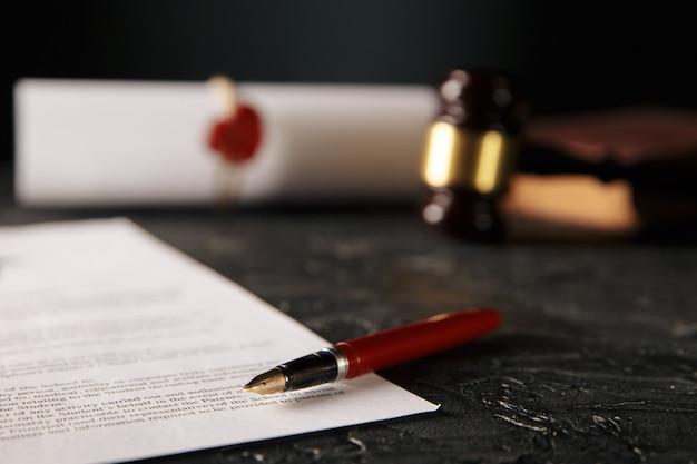 Documentos notariales con bolígrafo, martillo de madera y sello aislado