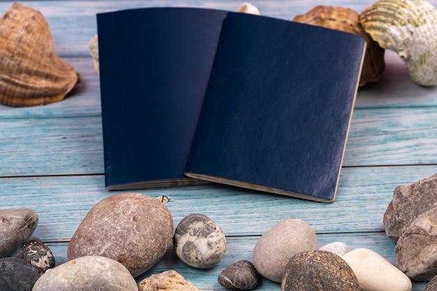 Documentos, piedras y conchas sobre un fondo de madera azul.tema de viaje