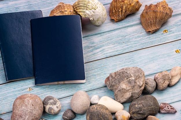 Documentos, piedras y conchas sobre un fondo de madera azul. tema de viaje.