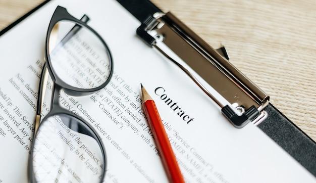 A documentos sobre una mesa de trabajo de madera con gafas y un lápiz rojo