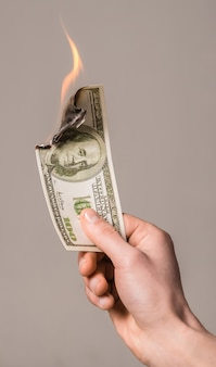 Dólar ardiente en mano aislado en gris