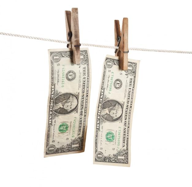 Dólar está colgando de una pinza de madera aislada en la superficie blanca