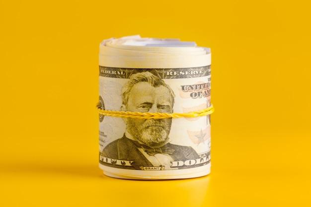 Dólar estadounidense dinero en efectivo sobre fondo amarillo.