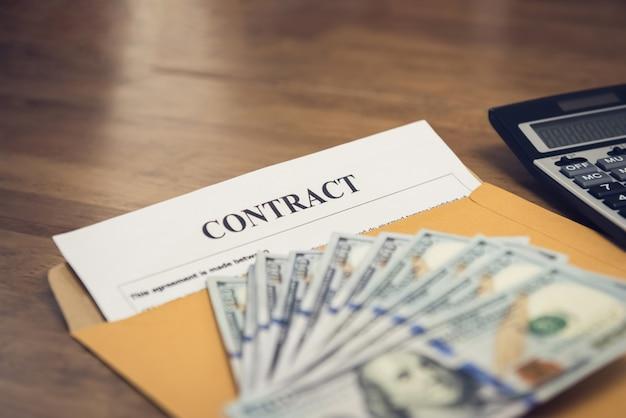 Dólar estadounidense en sobre marrón con documentos contractuales