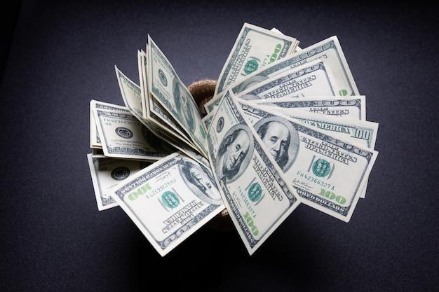 Dólares americanos dinero en efectivo en saco en mesa negra en el cuarto oscuro