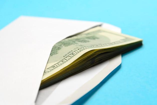 Dólares americanos en sobre postal blanco abierto en azul