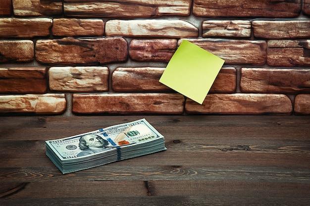 Dólares en billetes se apilan en una mesa cerca de la pared de ladrillo