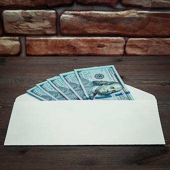 Dólares en billetes de cien dólares se extienden en un sobre sobre una mesa cerca de la pared de ladrillos.