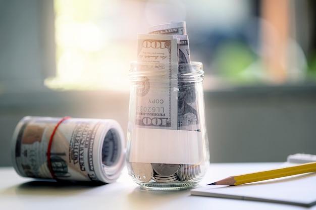 Dólares de billetes y monedas en la botella con nota de papel, lápiz sobre tabla blanca, guardar conceptos.