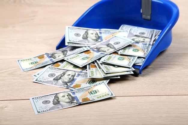Dólares en cuchara de basura sobre un piso de madera