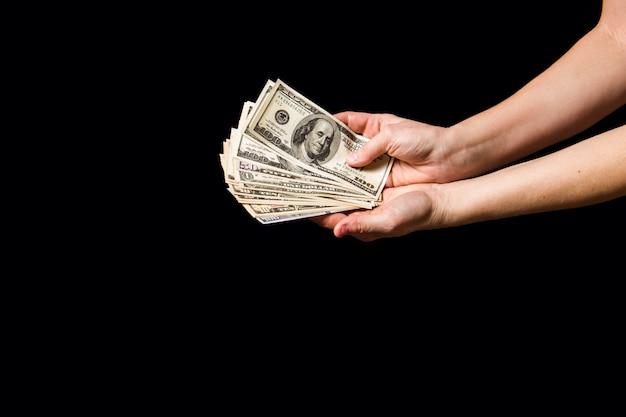 Dólares de dinero en las manos en la oscuridad