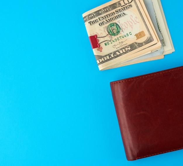 Dólares estadounidenses y billetera de cuero marrón sobre un fondo azul.