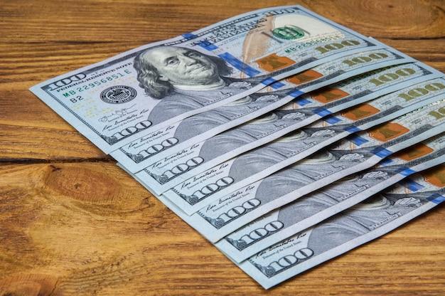 Dólares en una fila en diagonal sobre tablas de madera.
