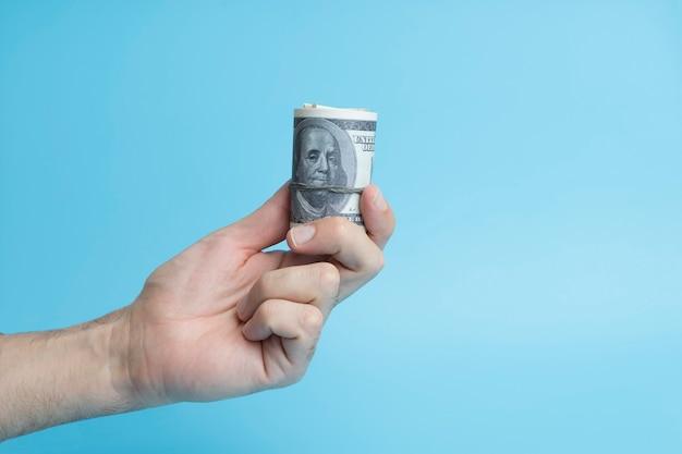 Dólares en la mano sobre un fondo azul moneda internacional y dinero de la renta de inversión de ee. uu ...