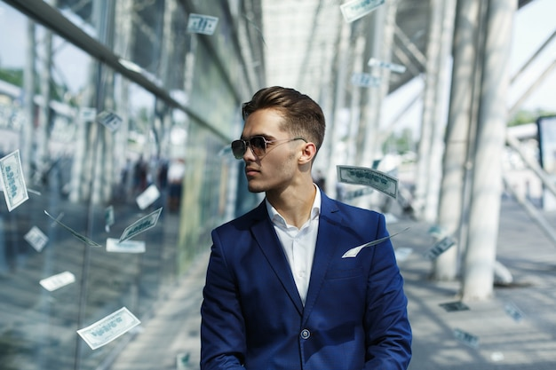 Dólares vuelan alrededor de apuesto joven empresario mientras camina por la calle