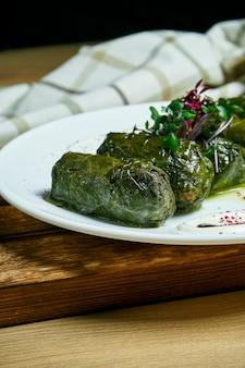 Dolma georgiano tradicional en hojas de parra con arroz y carne en un plato blanco sobre mesa de madera.