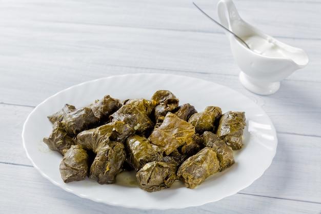 Dolma rellena de carne en hojas de uva en plato blanco y tazón con salsa de crema en la mesa de madera blanca
