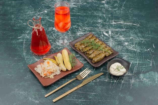 Dolma con vaso de jugo y crema agria sobre mesa de mármol.