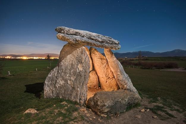Dolmen megalítico prehistórico en la noche en el norte de españa, noche estrellada en el fondo.