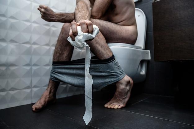 Dolor al sentarse en el inodoro en el baño. guy tiene estreñimiento y sufre. aprieta el papel higiénico. piel pálida. chico desnudo. pantalones cortos en los pies.