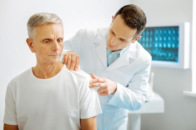 Dolor de articulaciones. doctor inteligente serio agradable de pie detrás de su paciente y mirando el hombro de su paciente mientras revisa las articulaciones