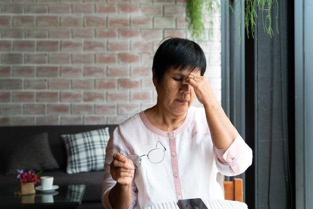 Dolor de cabeza de anciana mientras usa teléfono inteligente, cuidado de la salud