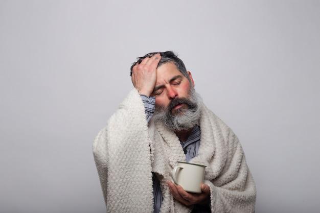Dolor de cabeza hombre. foto de un hombre enfermo envuelto en una manta con una taza de té caliente. concepto de salud.