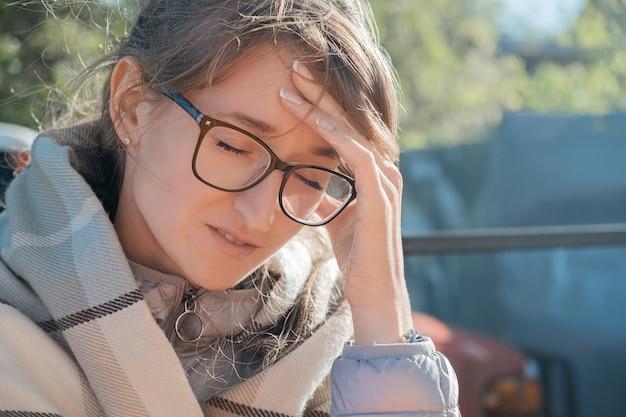 Dolor de cabeza, migraña, hipertensión. mujer adulta joven con gafas sosteniendo su cabeza mientras está sentado al aire libre envuelto en un plaid