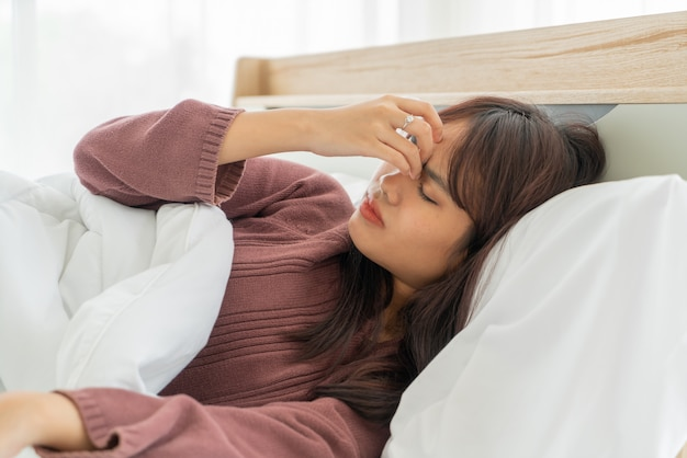 Dolor de cabeza de mujer asiática y dormir en la cama
