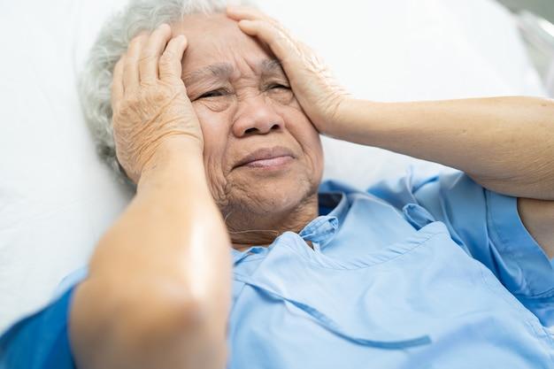 Dolor de cabeza del paciente asiático de la mujer mayor en el hospital.