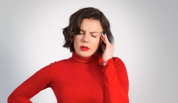 Dolor de cabeza. retrato de una joven cansada, se quita las gafas y se masajea la cabeza de la sien. fatiga y estrés.