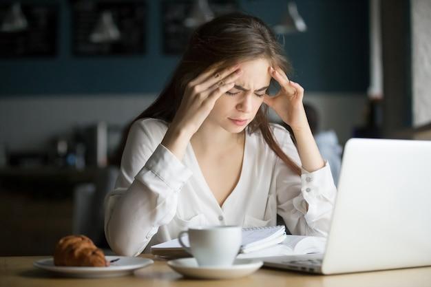 Dolor de cabeza subrayado nervioso del estudiante femenino que siente en café