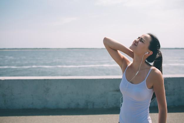 Dolor de cuello durante el entrenamiento. atleta corriendo corredor de mujer de cabello negro caucásico con lesión deportiva y tocando los músculos de la parte superior de la espalda afuera después del ejercicio en verano