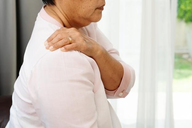 Dolor de cuello y hombro, anciana que sufre una lesión de cuello y hombro, concepto de problema de salud