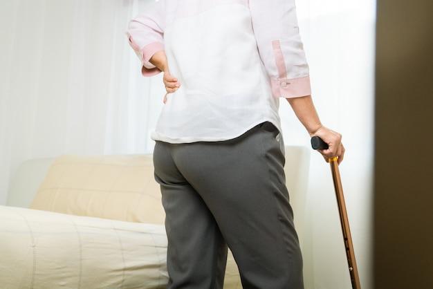 Dolor de espalda anciana sufre en casa, problema de salud del concepto senior