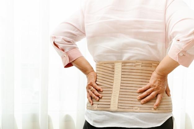 Dolor de espalda, mujer senior con cinturón de soporte en el fondo blanco