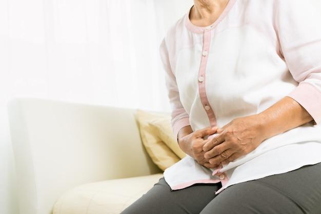 Dolor de estómago de anciana en casa, problema de salud del concepto senior
