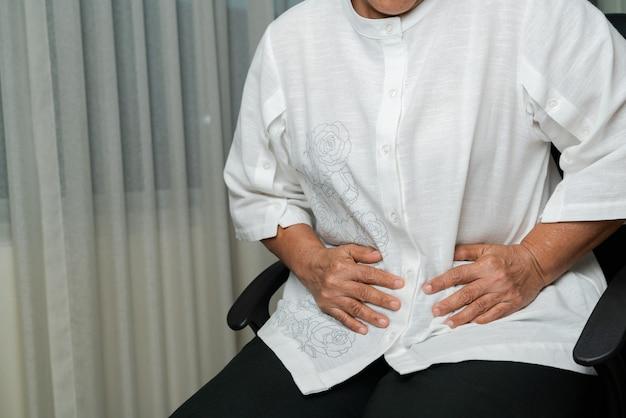 Dolor de estómago de la anciana en casa, problema de salud del concepto senior
