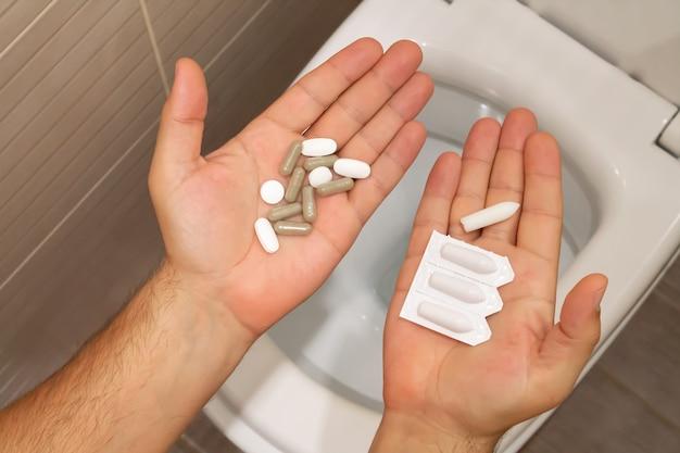 Dolor de estómago, estreñimiento, hemorroides o concepto de tratamiento de intoxicación alimentaria. hombre sujetando píldoras y supositorios vista superior