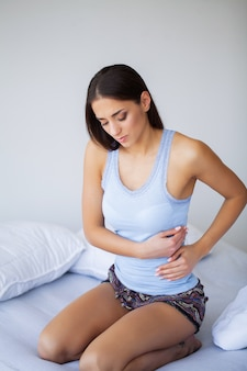 Dolor de estómago. joven insalubre con dolor de estómago apoyado en la cama en su casa