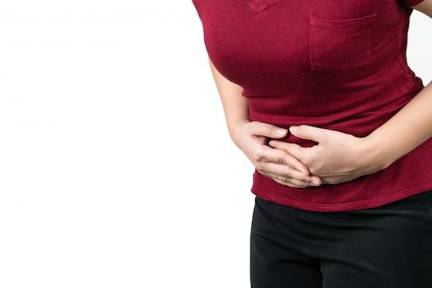 Dolor de estómago, mujer joven que sufre de dolor abdominal sintiendo síntomas de pms sobre fondo blanco.
