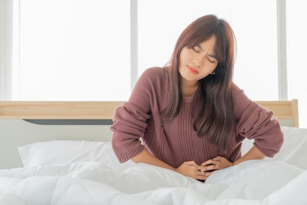 Dolor de estómago de las mujeres asiáticas y durmiendo en la cama
