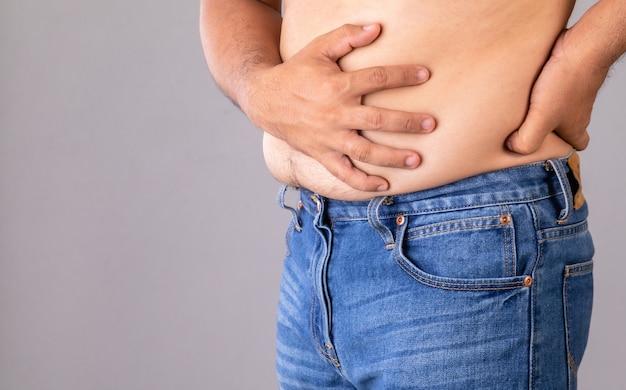 Dolor de estómago o dolor en el concepto de vientre: hombre gordo usando su mano y presionando sobre el estómago