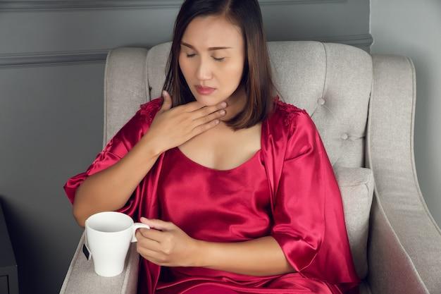 Un dolor de garganta es un dolor, arañazos o irritación, mujeres asiáticas en ropa de dormir de seda roja con reflujo ácido por la noche