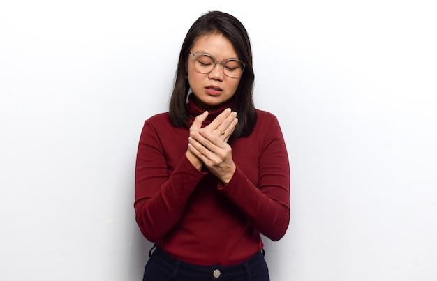Dolor en el gesto de la mano de las mujeres asiáticas hermosas jóvenes visten camisa roja aislada sobre fondo blanco