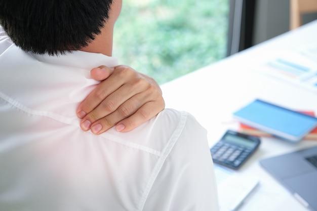 Dolor de hombro también conocido como síndrome de oficina, el hombre muestra dolor muscular durante el trabajo.